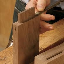 The tenon is getting a few final passes with the chisel in order to assure that it fits perfectly into the mortised slot.